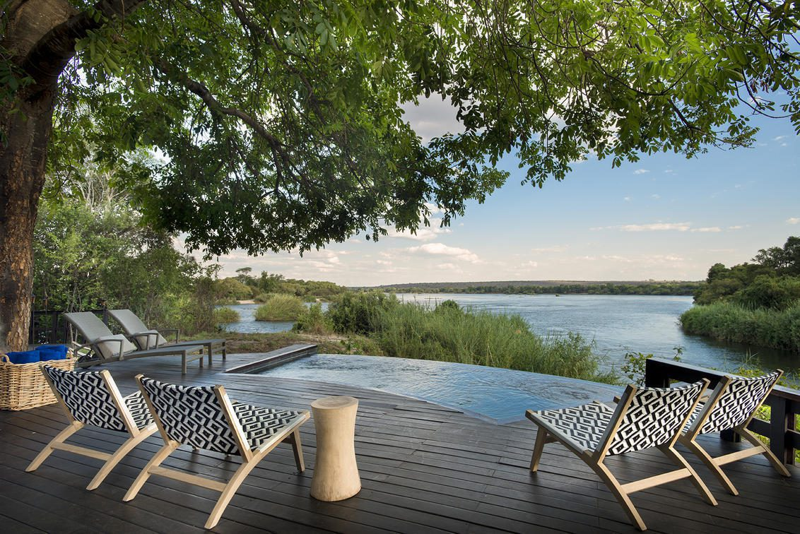 deck with lounge chairs and pool overlooking river on Pan-African safari