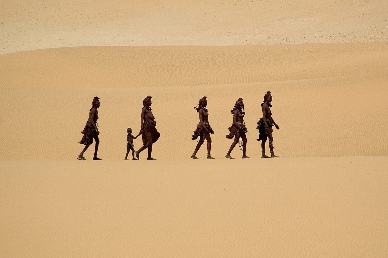 Himba tribe walking through the endless desert seen on our cultural safari