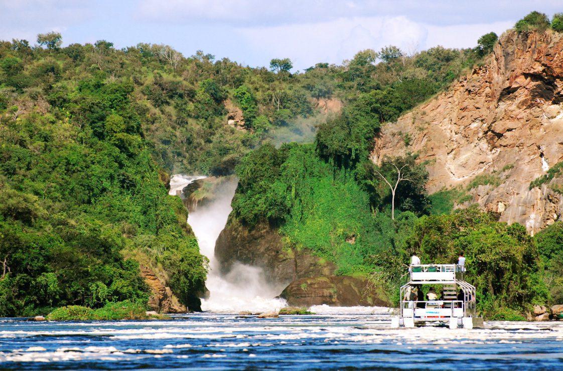 double decker boat cruising near Murchison Falls coming down through the green hillside on safari in Uganda