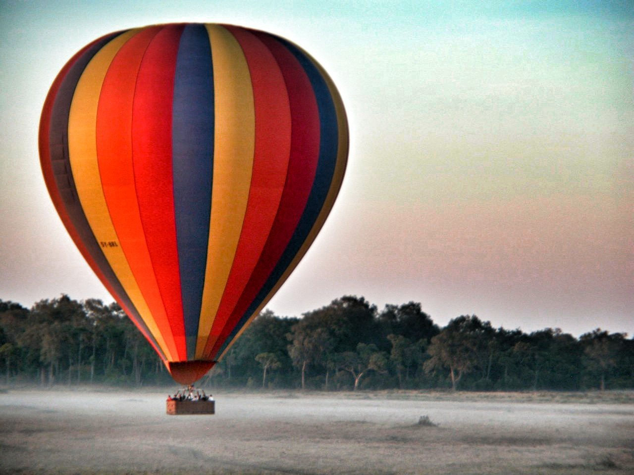 hot air balloon hovers closely above the ground in front of a pastel sky