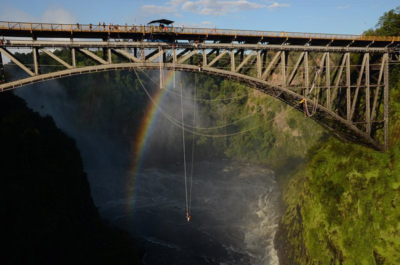 victoria falls bridge with rainbos and bungee jumper hanging low