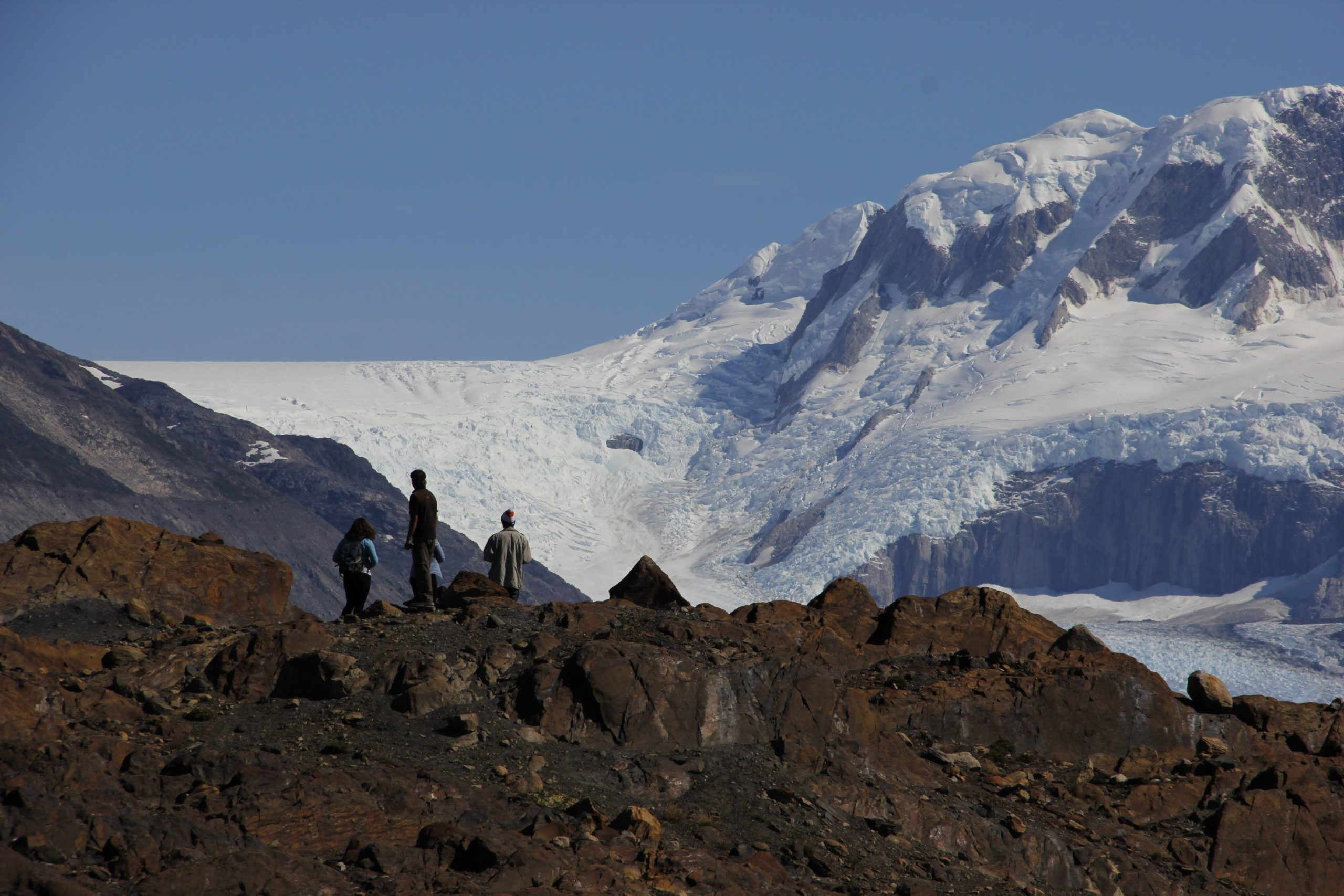 group of hikers treking through mountains with glacier in background