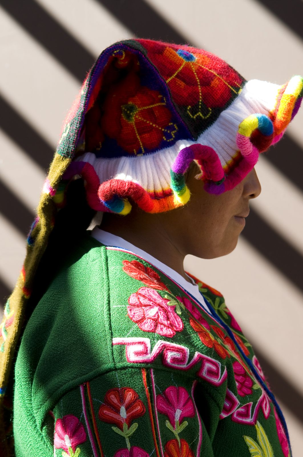 Peruvian woman standing, dressed in colorful woven clothes