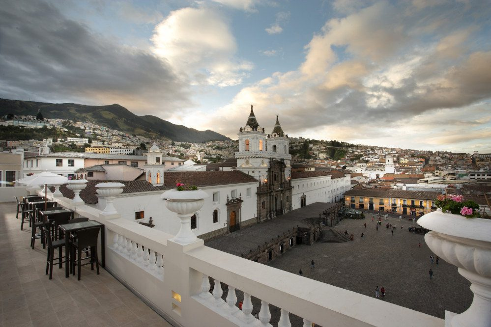 roof top and balcony with buildings and clouds in the background on this Ecuador tour