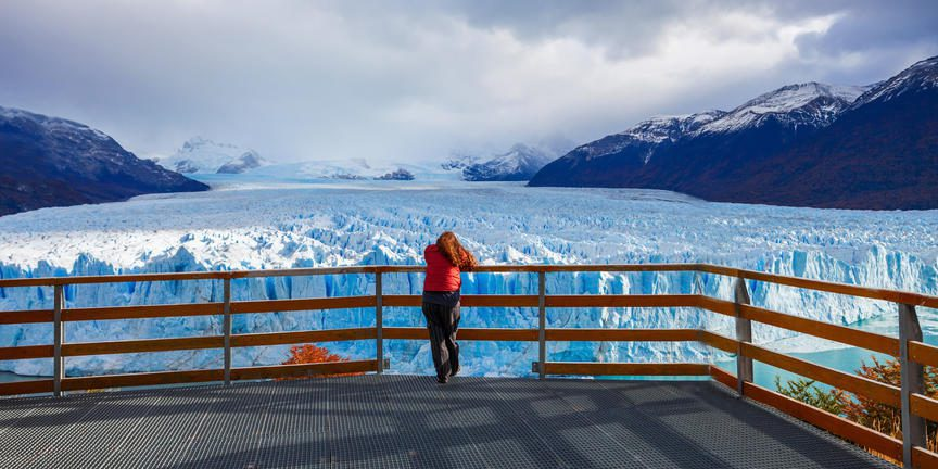 woman in red jacket looks over ice fields covered in cloud in El Calafate seen on this Argentina & Chile holiday