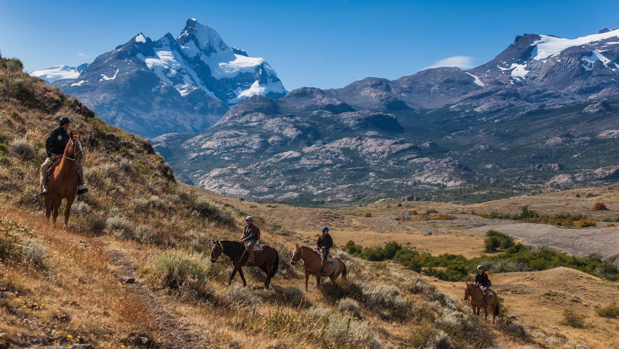 small group of people on horseback riding through mountains