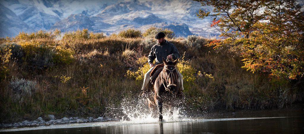 man on horseback running through water
