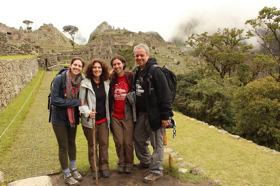 family safari members standing in the fog at machu picchu citadel