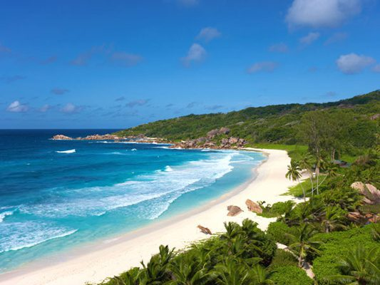 tropical beach with white sand and green trees Anse Source D'Argent Beach