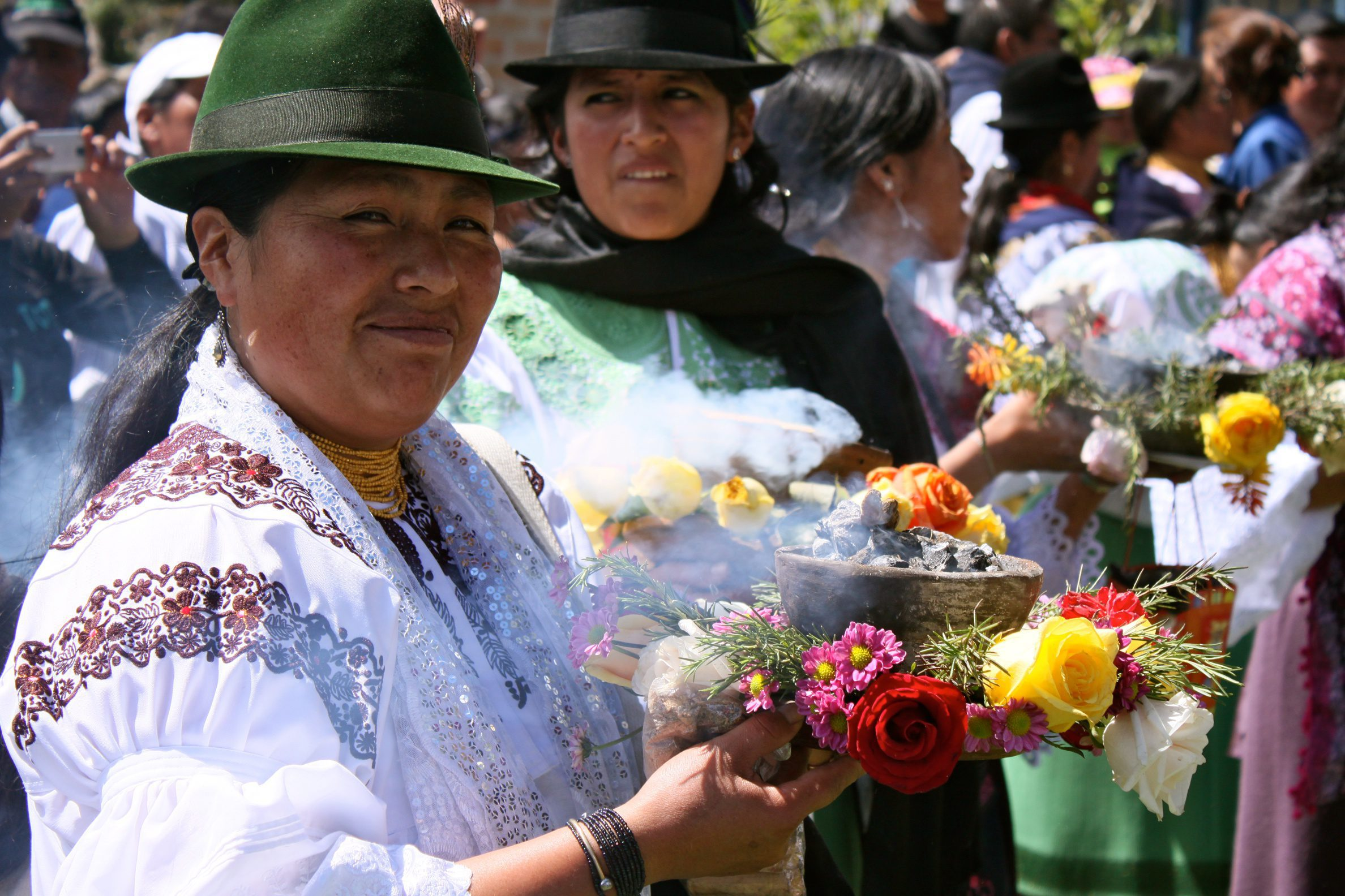 two women holding flowers at a marketplace