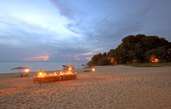 candle lit dinner on the beach with setting sun over Lake Tanganyika
