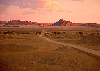 open desert with winding road and rocks in the distance at sunset on safari in namibia