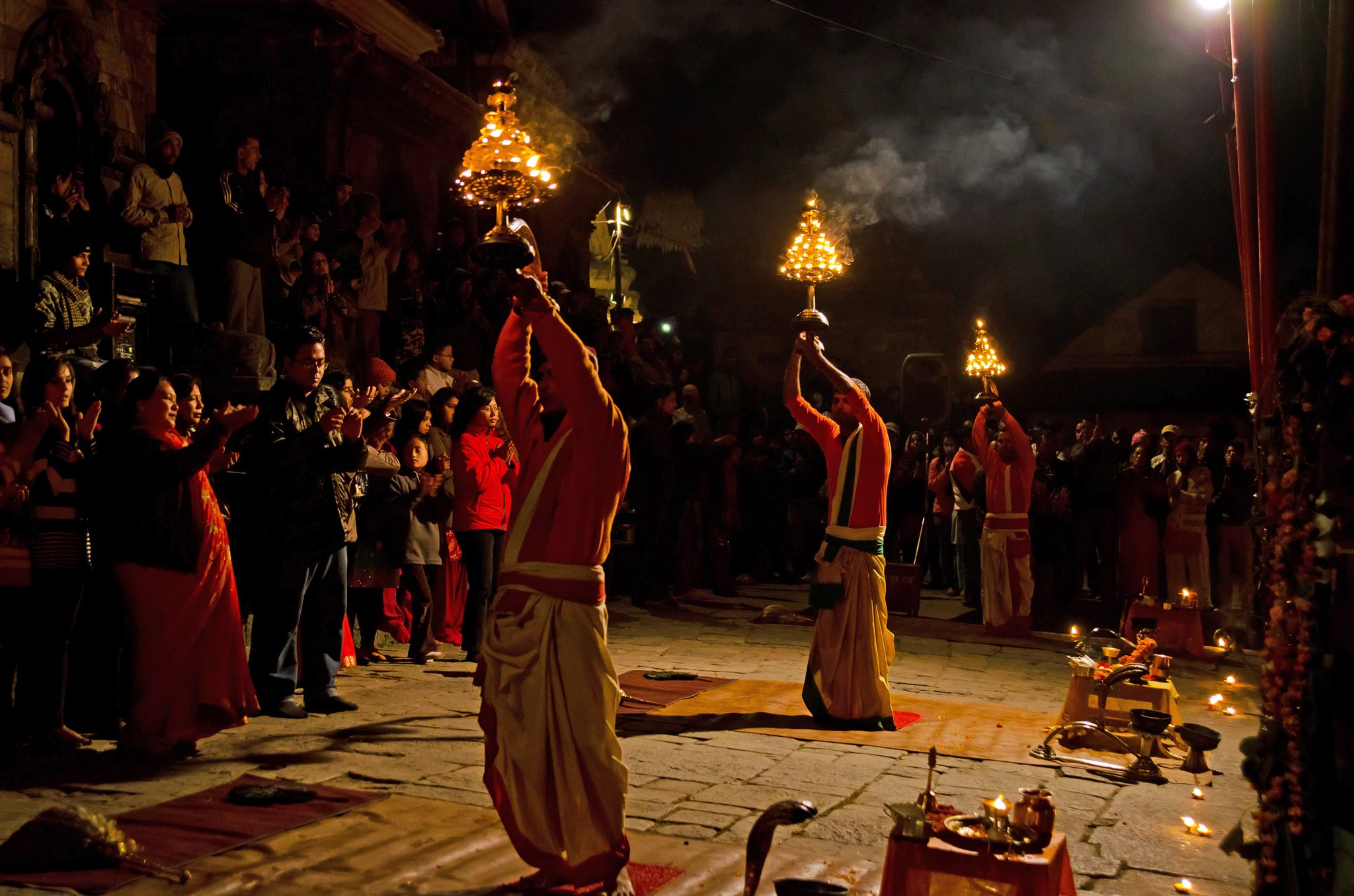 three holy men carrying torches in a procession during a ceremony at Pashupatinath Temple seen on safari in nepal