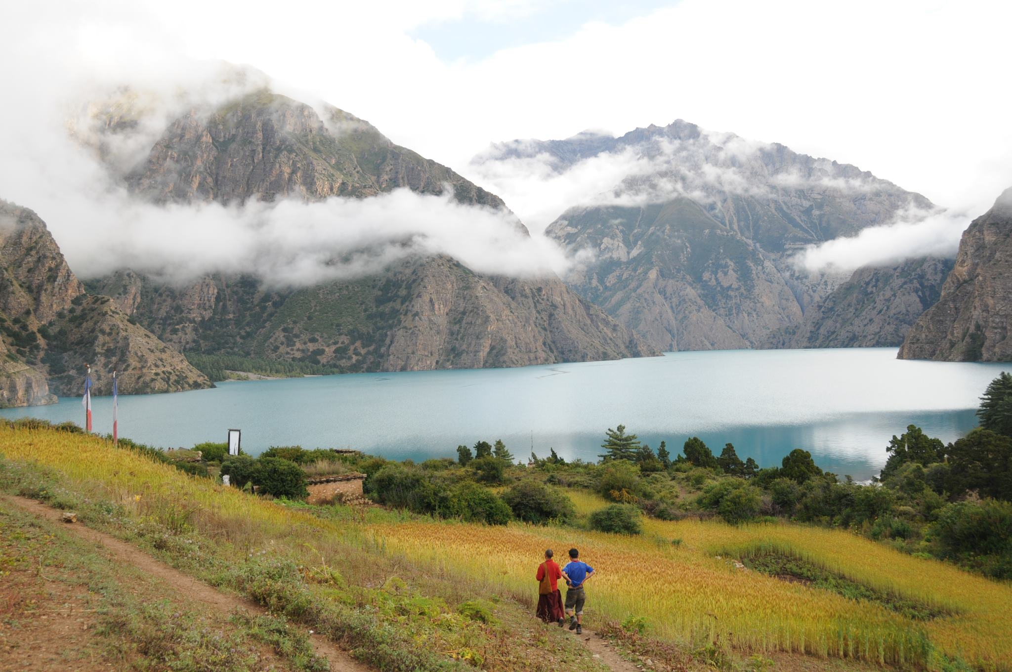 two people walking through the hillside with trees, Phuksundo Lake, and mountains in the background seen on nepal safari