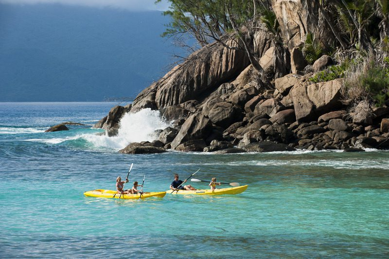 two canoes in aqua water passing by rocks and palm trees seen on Madagascar canoeing safari