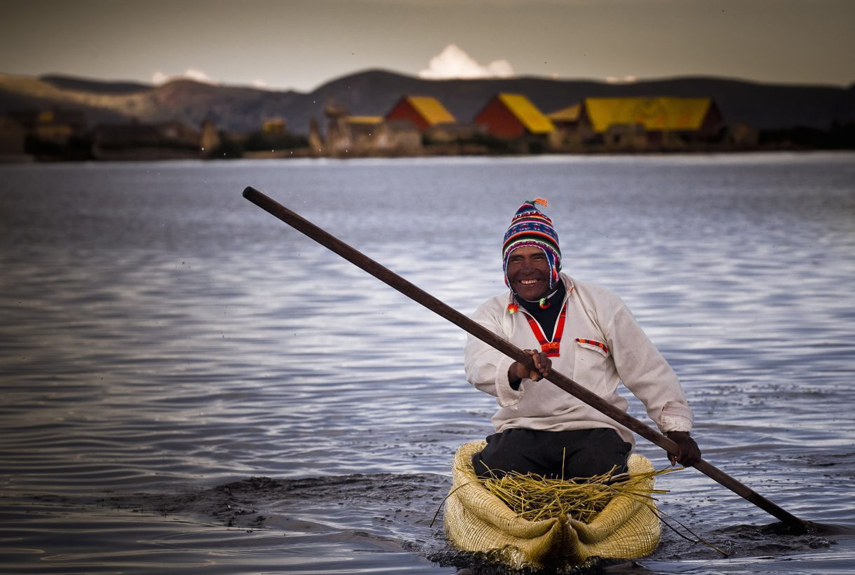 man in traditional attire and reed kayak on lake titicaca