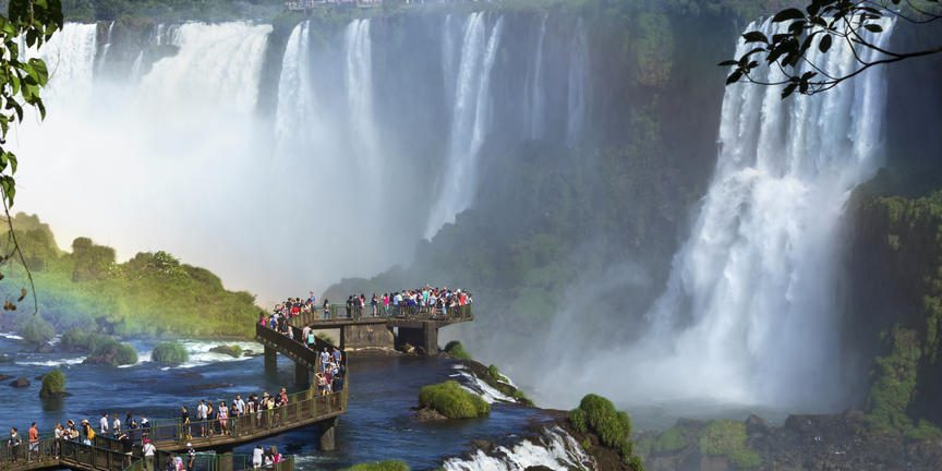 Tourists on a bridge overlooking waterfall at Iguazu Falls as rainbow peaks through on safari in Argentina