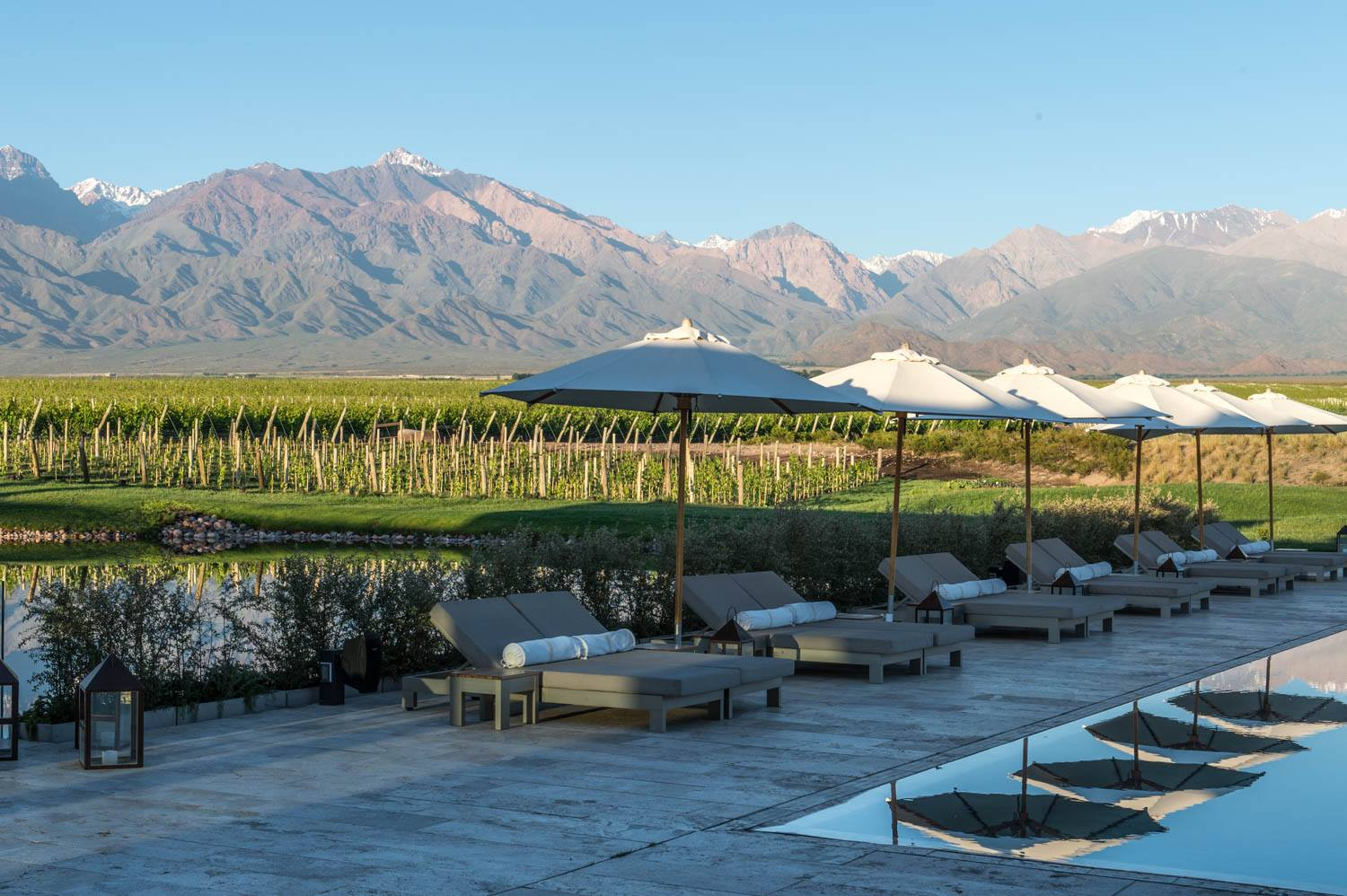 pool deck with chairs and umbrellas with vineyards and mountains in the background