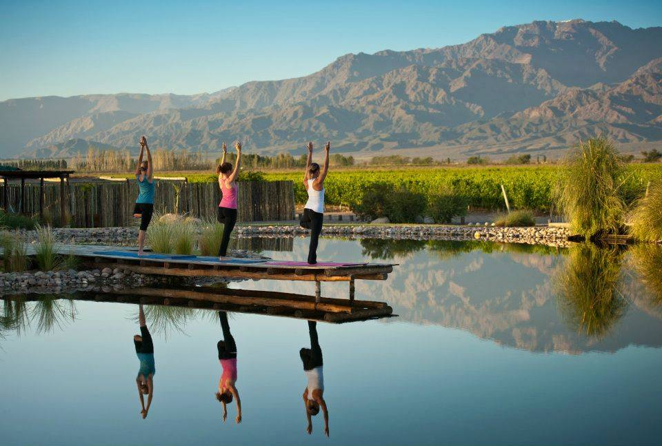 three women doing yoga with mountains in background and water in foreground