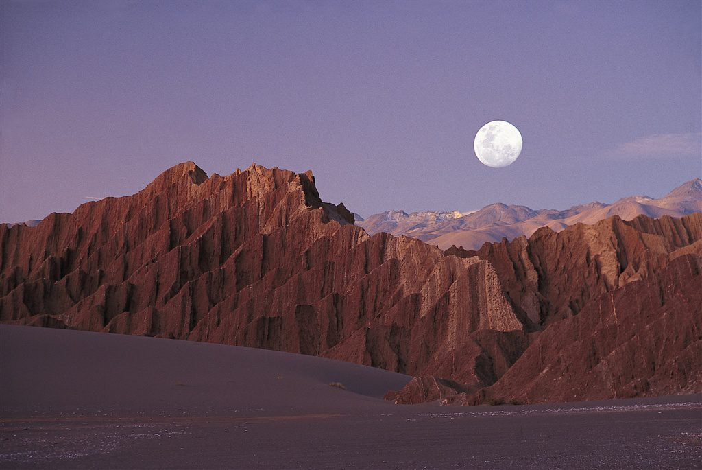 moon over red mountains in the desert on Chile safari