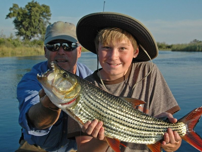 boy with his dad proudly showing off a tiger fish