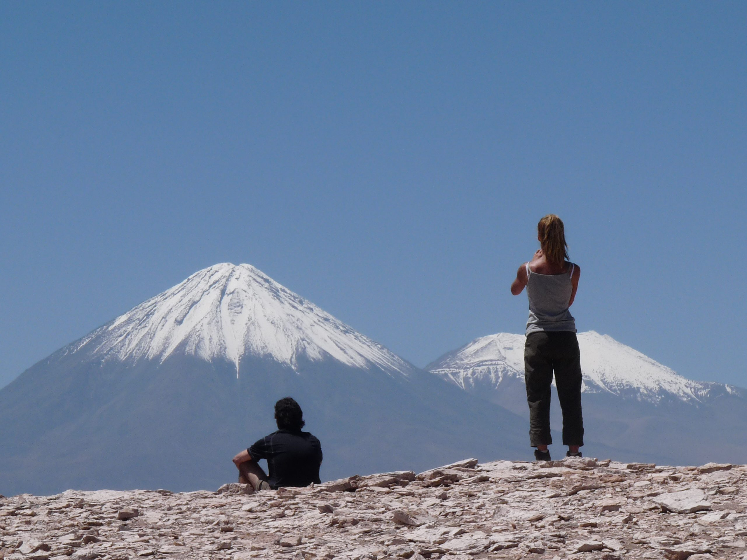 two people with snow capped mountains in the background
