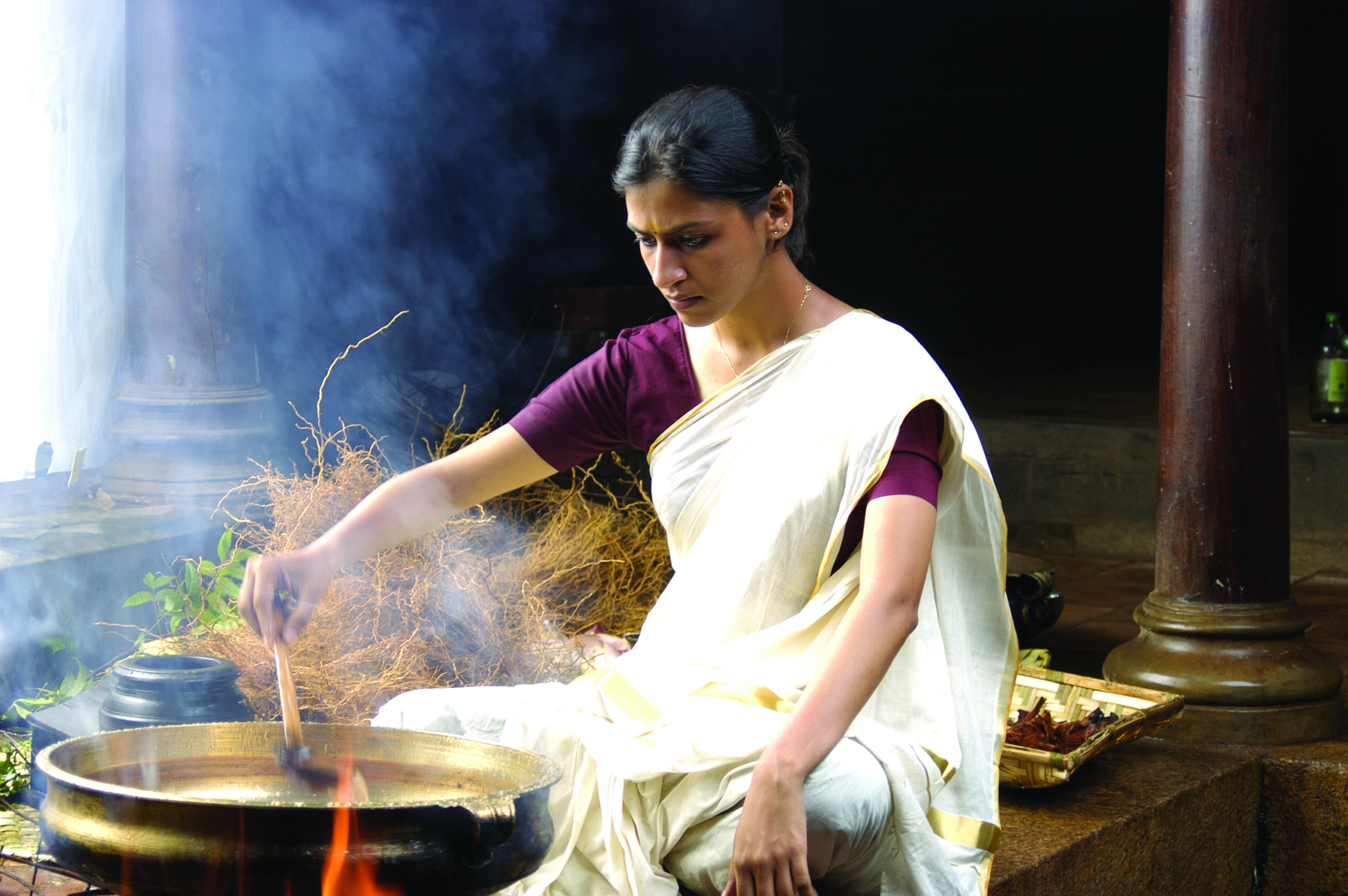 woman stirring a smoking pot over an open fire in a white saree and purple shirt