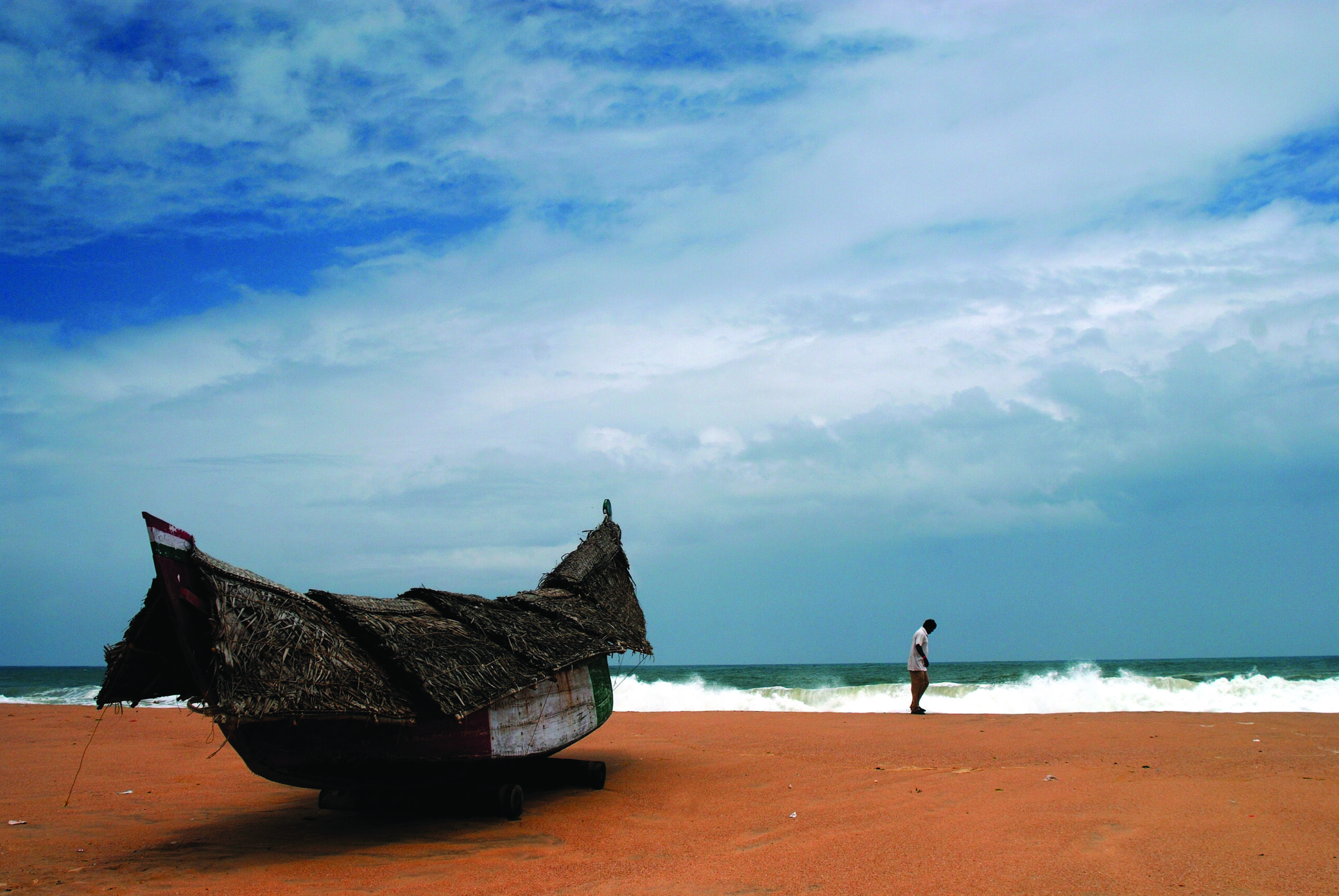 traditional boat sitting on an orange sand beach with a small figure near crashing surf on the beach in the background