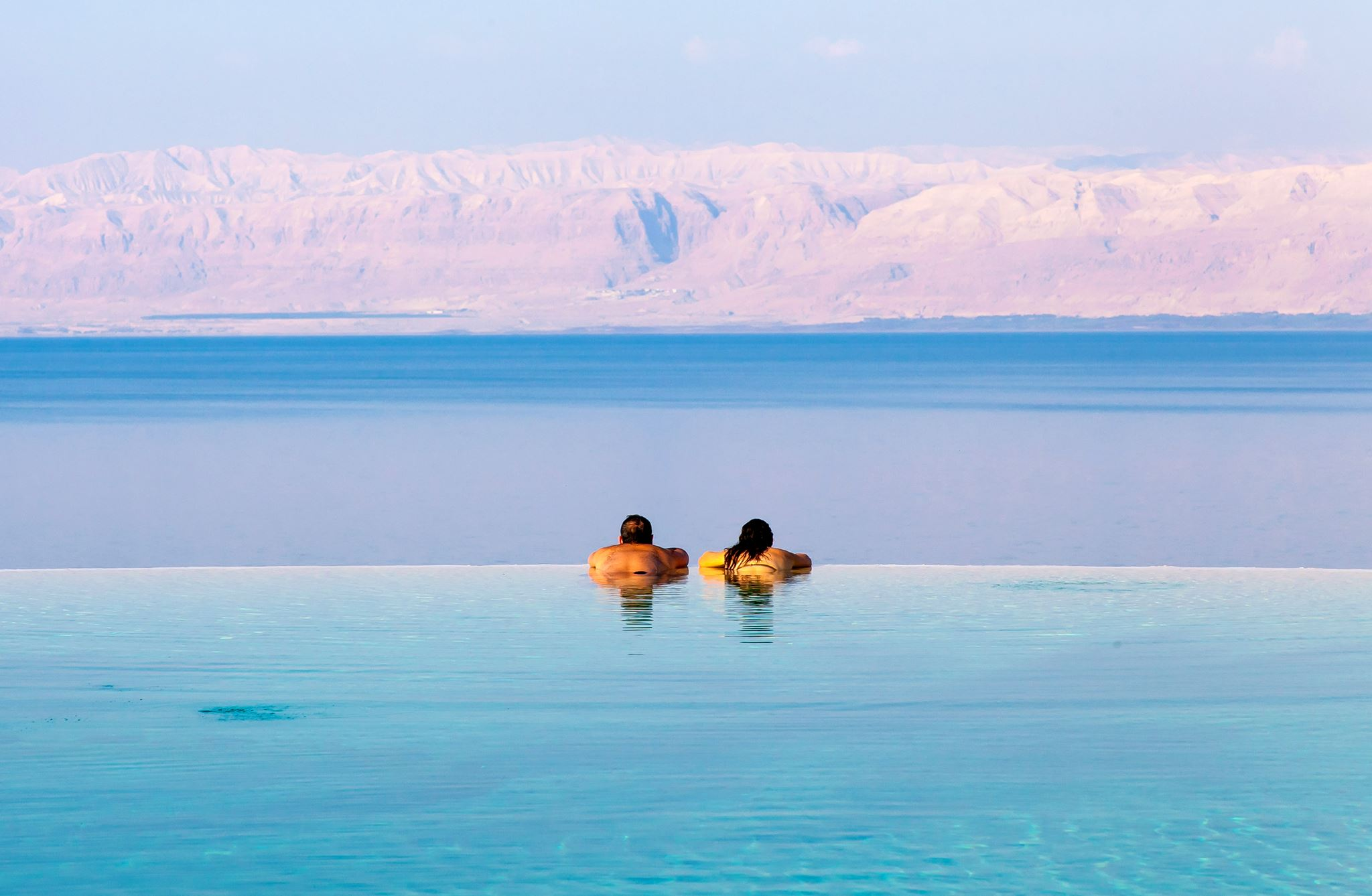 man and woman at kempinski hotel dead sea infinity pool