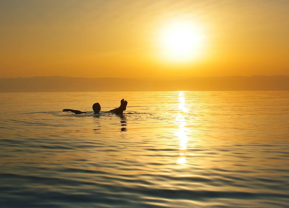 person floating in the dead sea at sunset