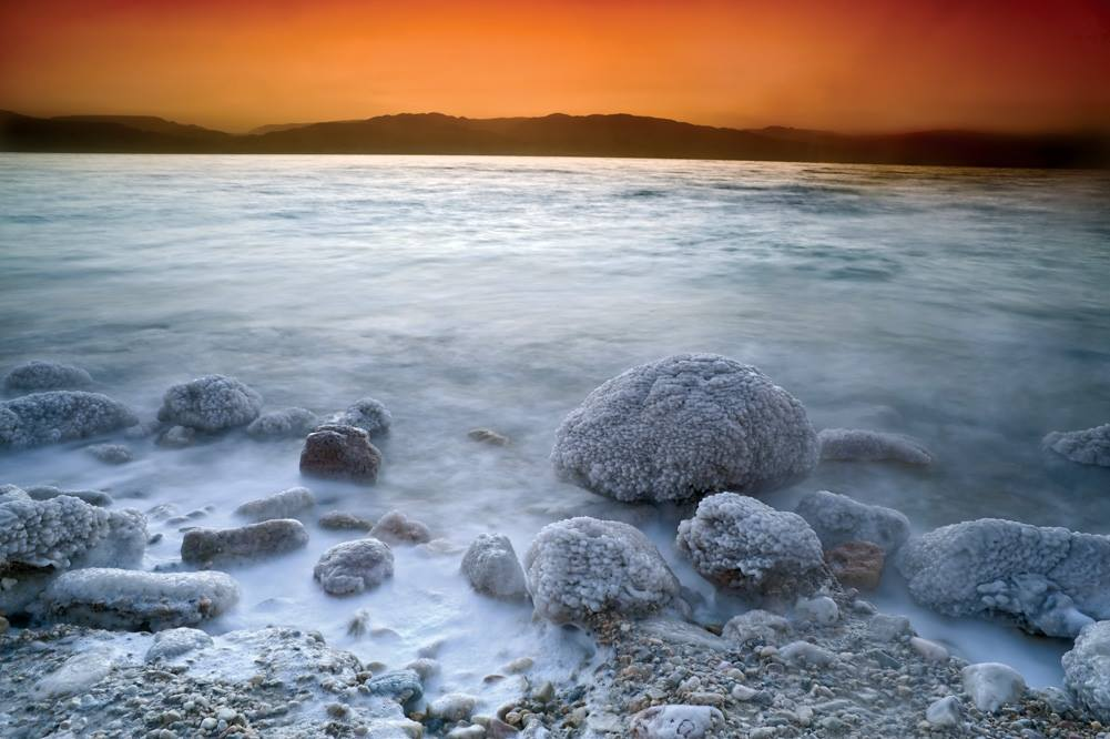 rocks coated in salt at shore of dead sea at sunset