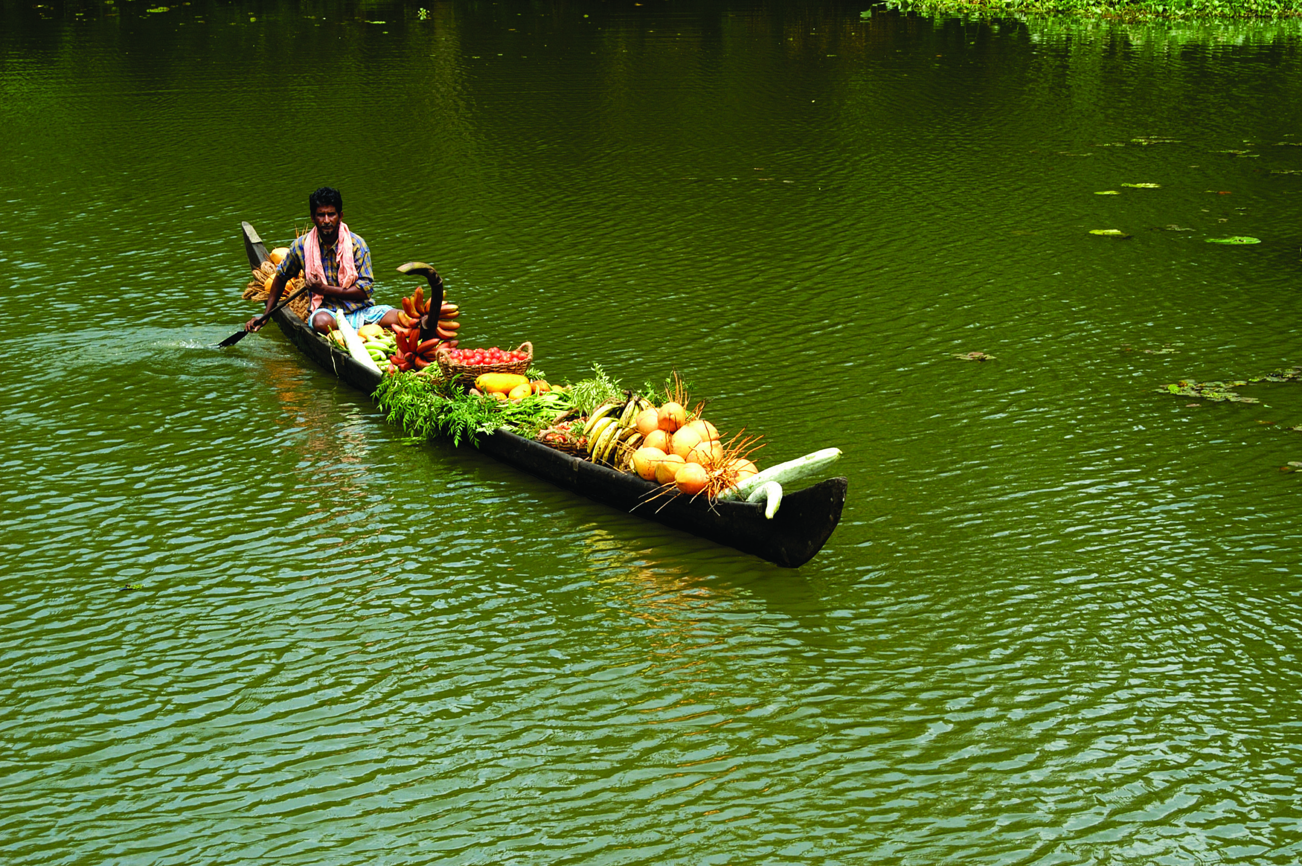 man in a longboat selling vegetables in green calm water