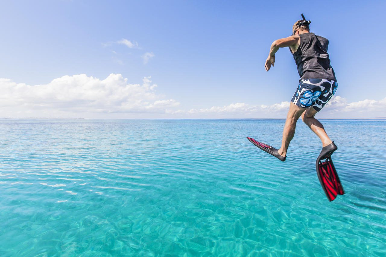 snorkeler jumping into the turquoise water