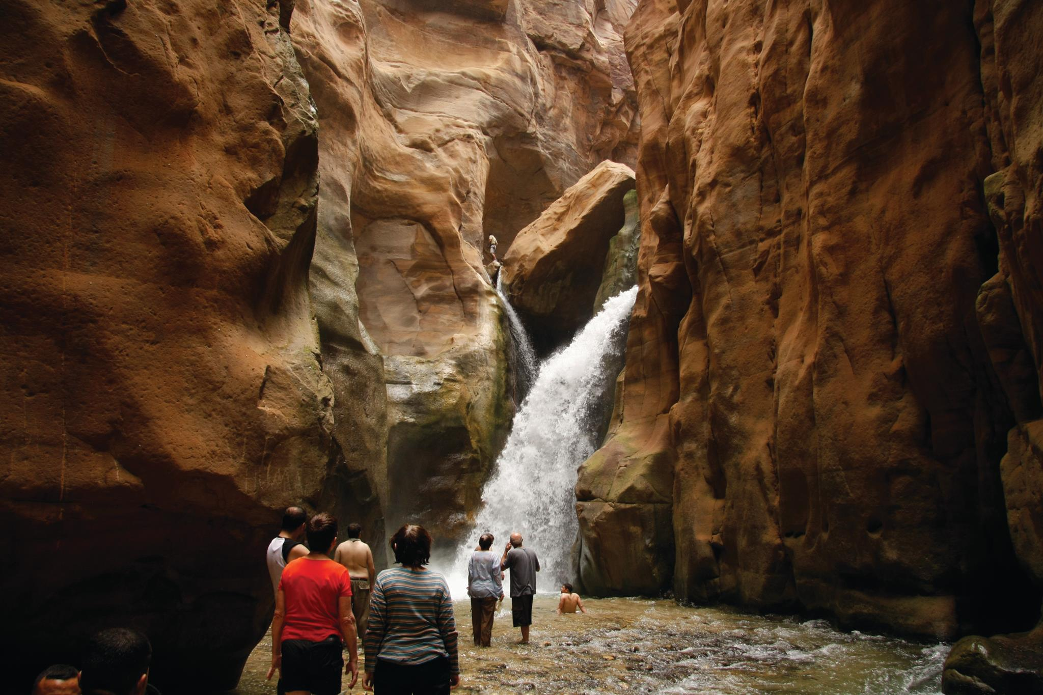 tourists looking at a waterfall in the desert