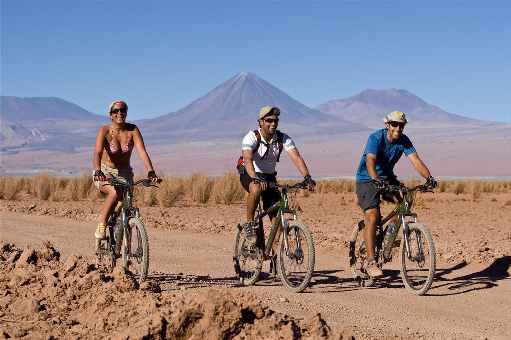 three people biking through the Atacama with the mountains in the background