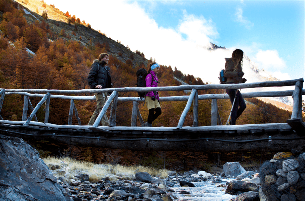 three people crossing a footbridge with a mountain slope behind them
