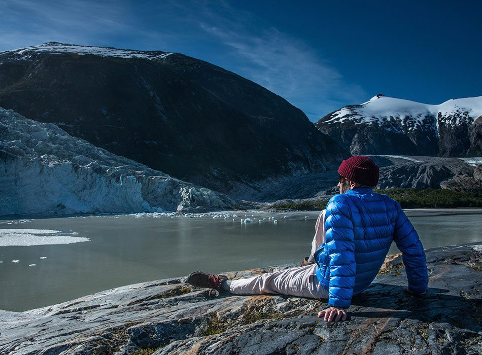 man sitting on a rock looking at a glacier