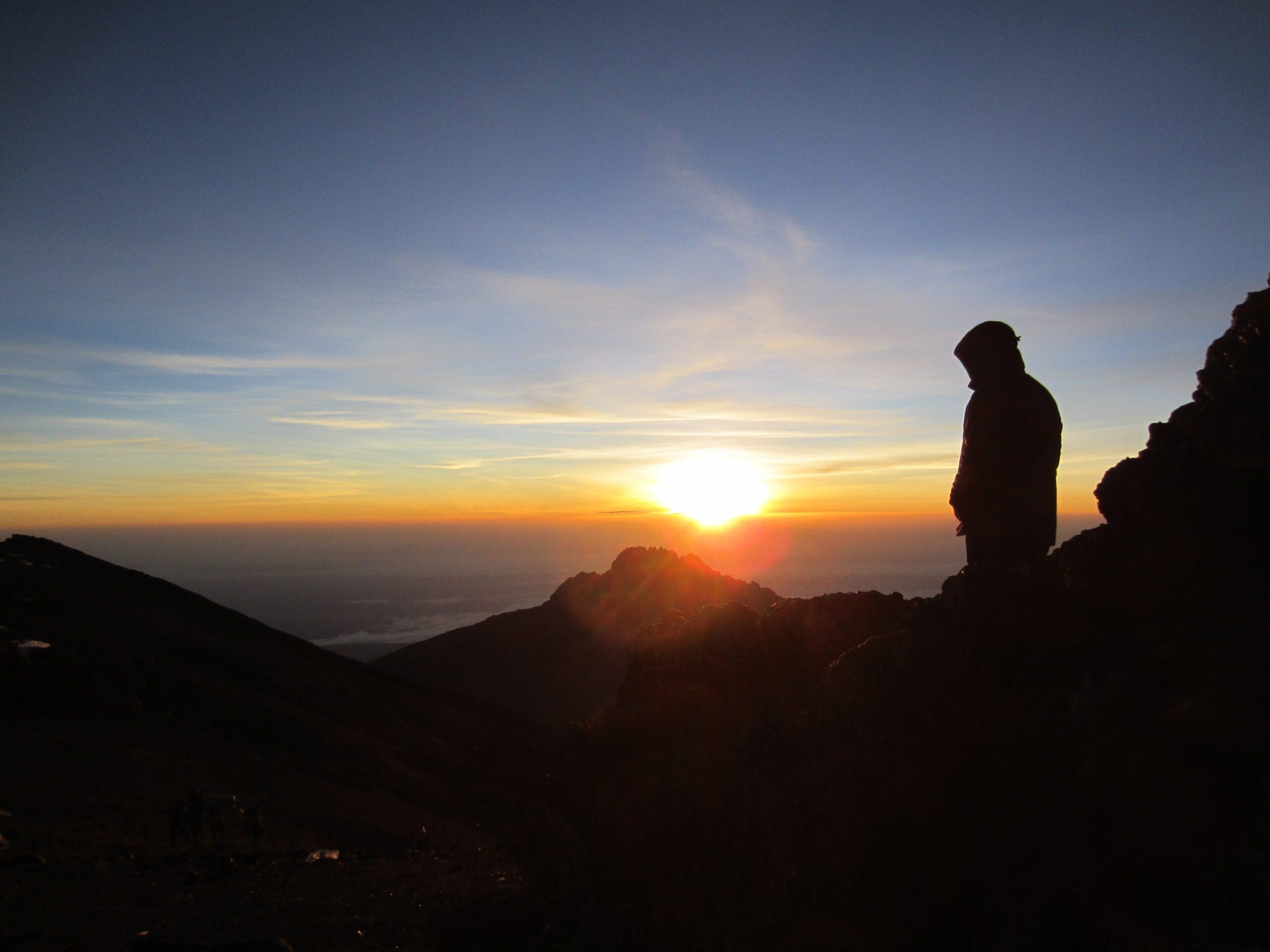 shadow of a woman standing atop Mt. Kilimajaro admiring the sunrise below.