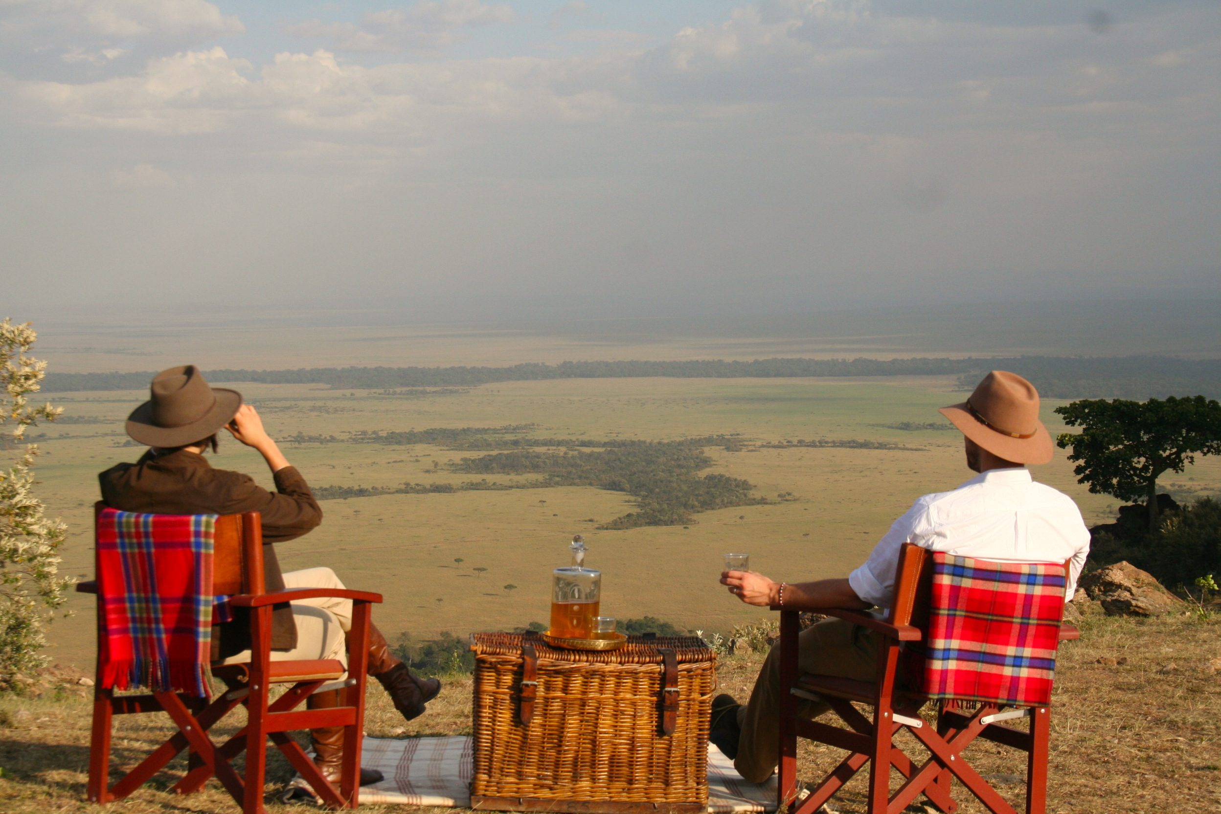 two people sit in chairs with blankets strewn over the back and enjoy a picnic overlooking the Maasai Mara