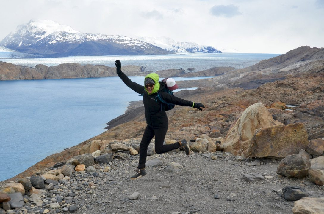 Woman jumping with joy in Patagonia with blue river in the background