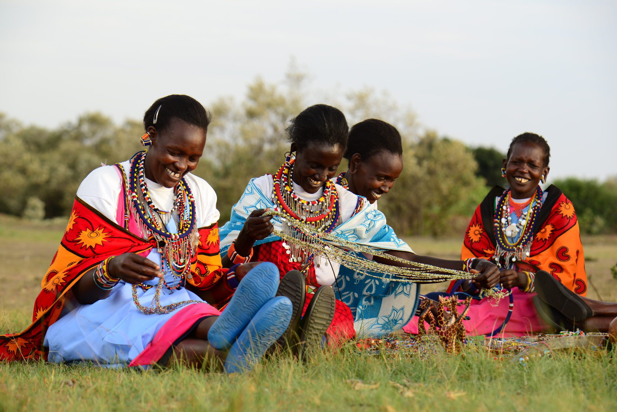group of brightly dressed Maasai women beading while sitting in the grass