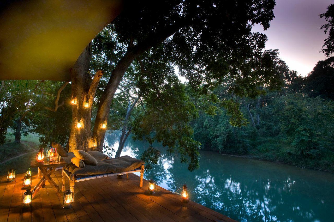 kerosene lanterns light the deck of banjaar tola tented camp overlooking the banjaar river, on India holiday