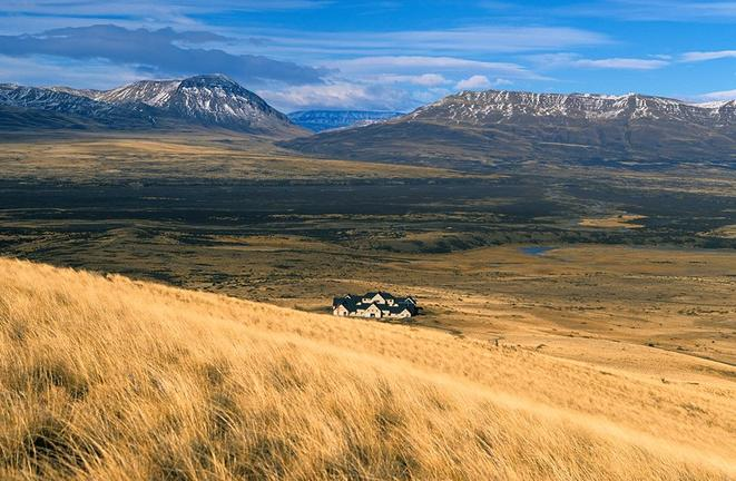 grassy plains with mountains and the background and a lodge on Argentina & Chile tour