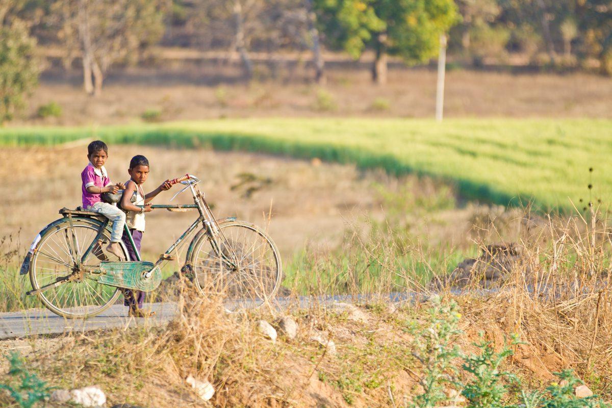 Seen on india safari are two children sharing a bike riding through the fields near Jamtara Safari Camp