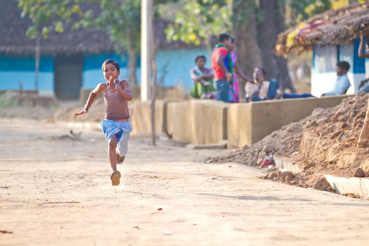 child running down the road in jamtara village seen on India safari