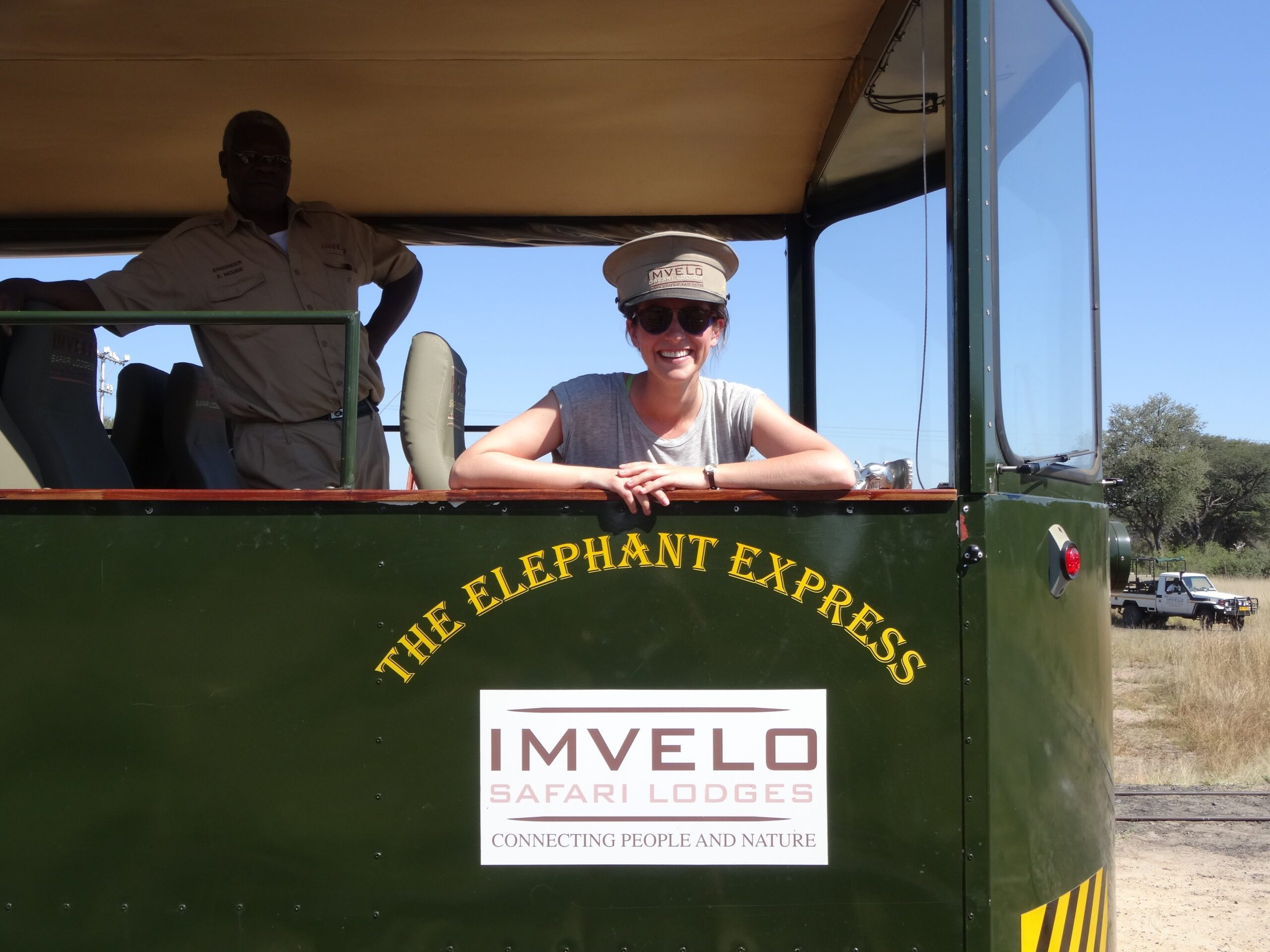 woman wearing an engineer's hat looking out the back of the Elephant Express