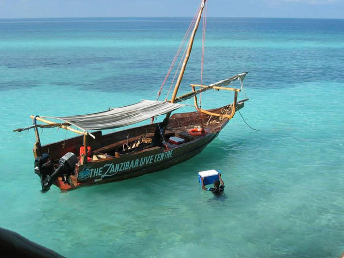 single dhow floating on the clear waters off zanzibar with a man in the water