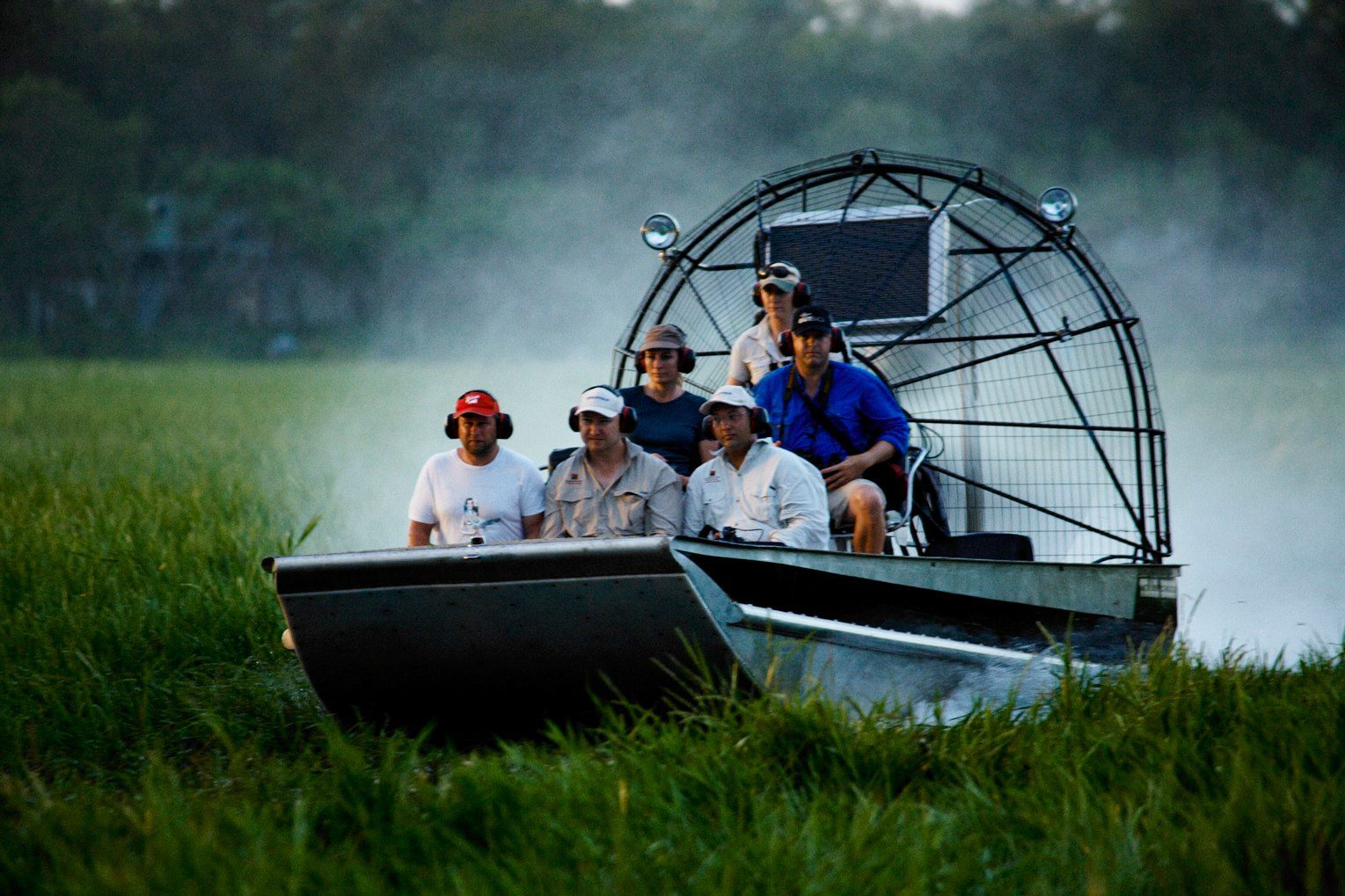 A group of people ride in an airboat across the floodplains in Kakadu National Park on a northern Australia holiday