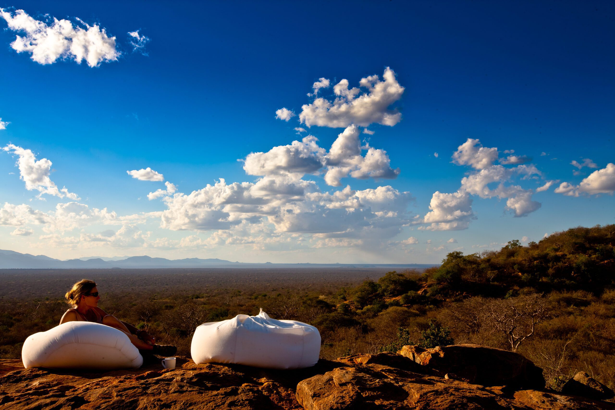 perfect blue sky with fluffy white clouds and two white bean bags set up to enjoy drinks.