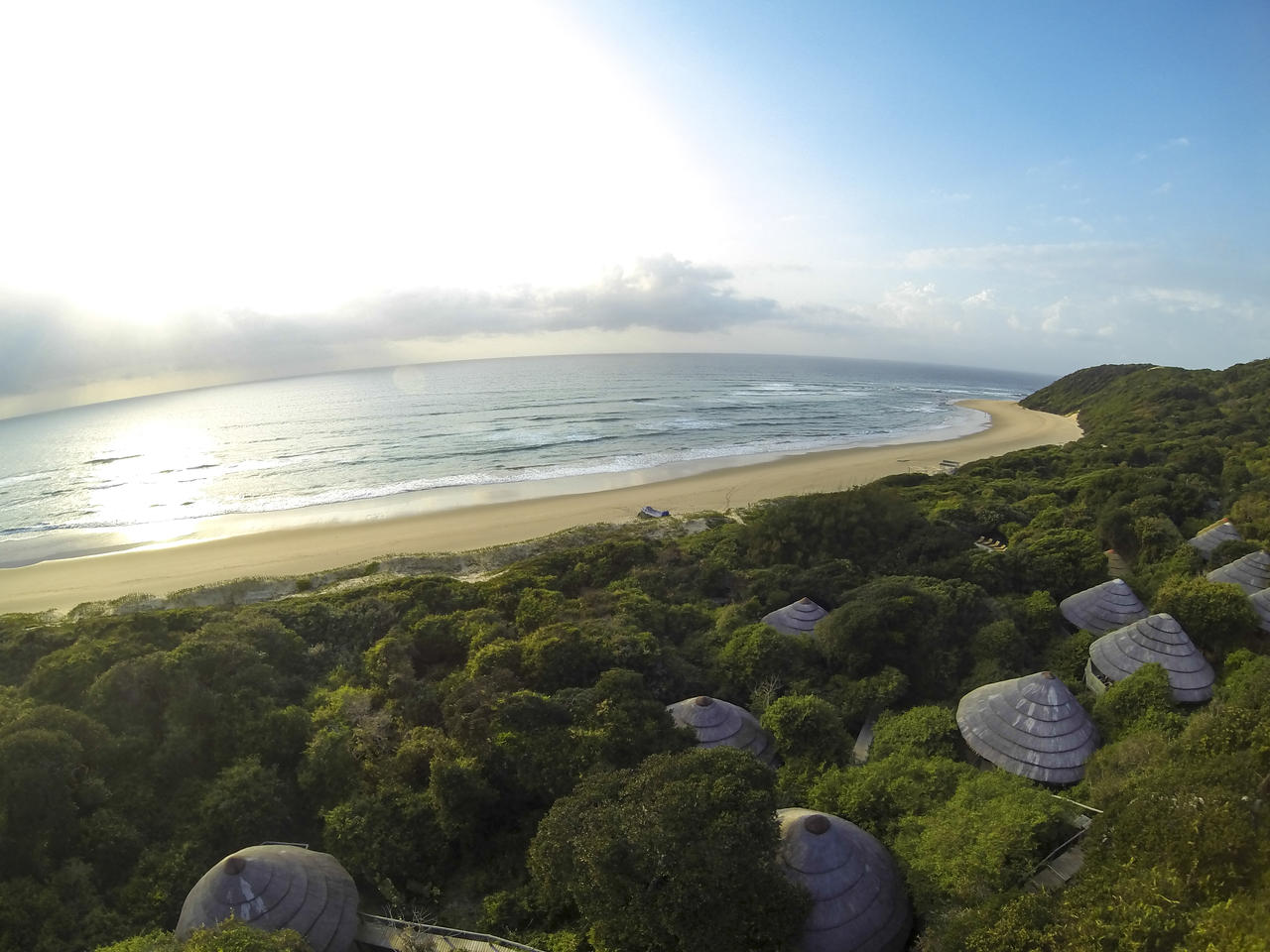 sunny aerial view of thonga beach lodge overlooking green lush trees and sandy beach